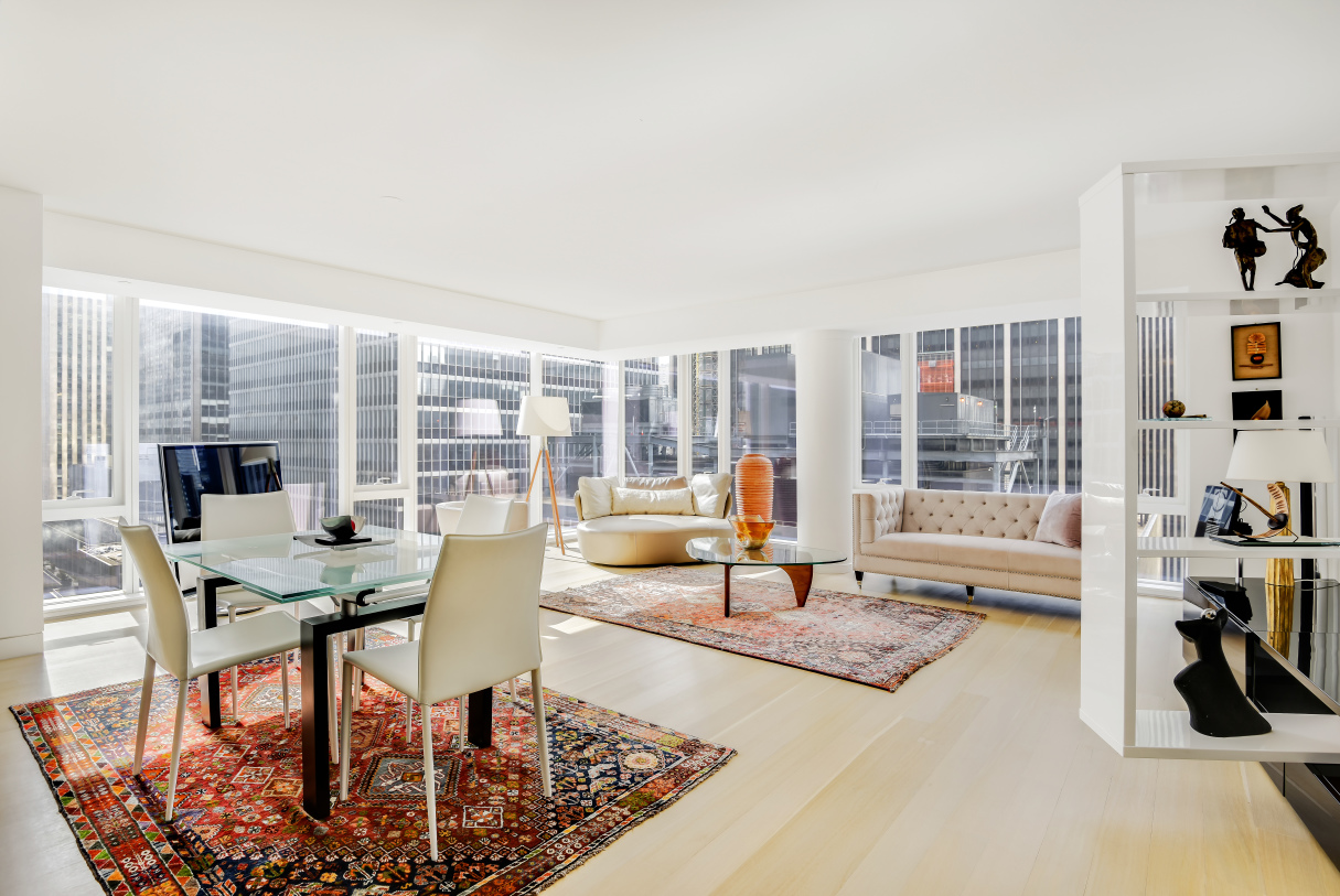 """Stunning 1,432 square foot, 2-bedroom, 2-bathroom residence, tastefully furnished with all the amenities of modern luxury – the perfect retreat in the heart of Midtown Manhattan. This mint condominium home offers luxurious design and finishes throughout, including rift-sawn 5-inch white oak plank flooring. From the entry foyer, which includes a spacious double-door coat closet, a gallery leads into the corner Great Room where floor to ceiling windows showcase exceptional south- and east-facing views of the city. For seamless living and entertaining, the living area melds with the open chef's kitchen, which features Italian walnut and custom white back-painted glass cabinetry, Calacatta Vision polished marble countertops, Watermark fixtures, and premier appliances by Miele. The Great Room is also fully outfitted with a state-of-the-art Bang & Olufsen BeoLab Sound System, a 40"""" Bang & Olufson BeoVision 10 Television, and high-end furnishings from Roche Bobois and more. The luxurious Master Suite is filled with light from a wall of south-facing floor to ceiling windows, and has ample space for any wardrobe with multiple deep closets. The en suite master bath, accessed through custom Rimadesio white glass pocket doors, has radiant-heated Siberian White marble flooring, a custom vanity topped with Siberian Mink stone, imported Italian Fantini fittings and fixtures, a soaking tub, and separate walk-in shower. The second bedroom is generously proportioned, with south-facing exposures and beautiful natural light. A second full bathroom and in-unit Miele washer and dryer complete this well-appointed home. 135 West 52nd Street offers residents a host of amenities, including a 12,000 SqFt Private Residents Club, 75-Foot Indoor Swimming Pool, State-of-the-Art Fitness Center, Luxurious Spa, Children's Playroom, Golf Simulator, and 24-hour Doorman and Concierge Services. Offered fully furnished, minimum lease term 6 months. Showings by appointment only – available for an August 1"""