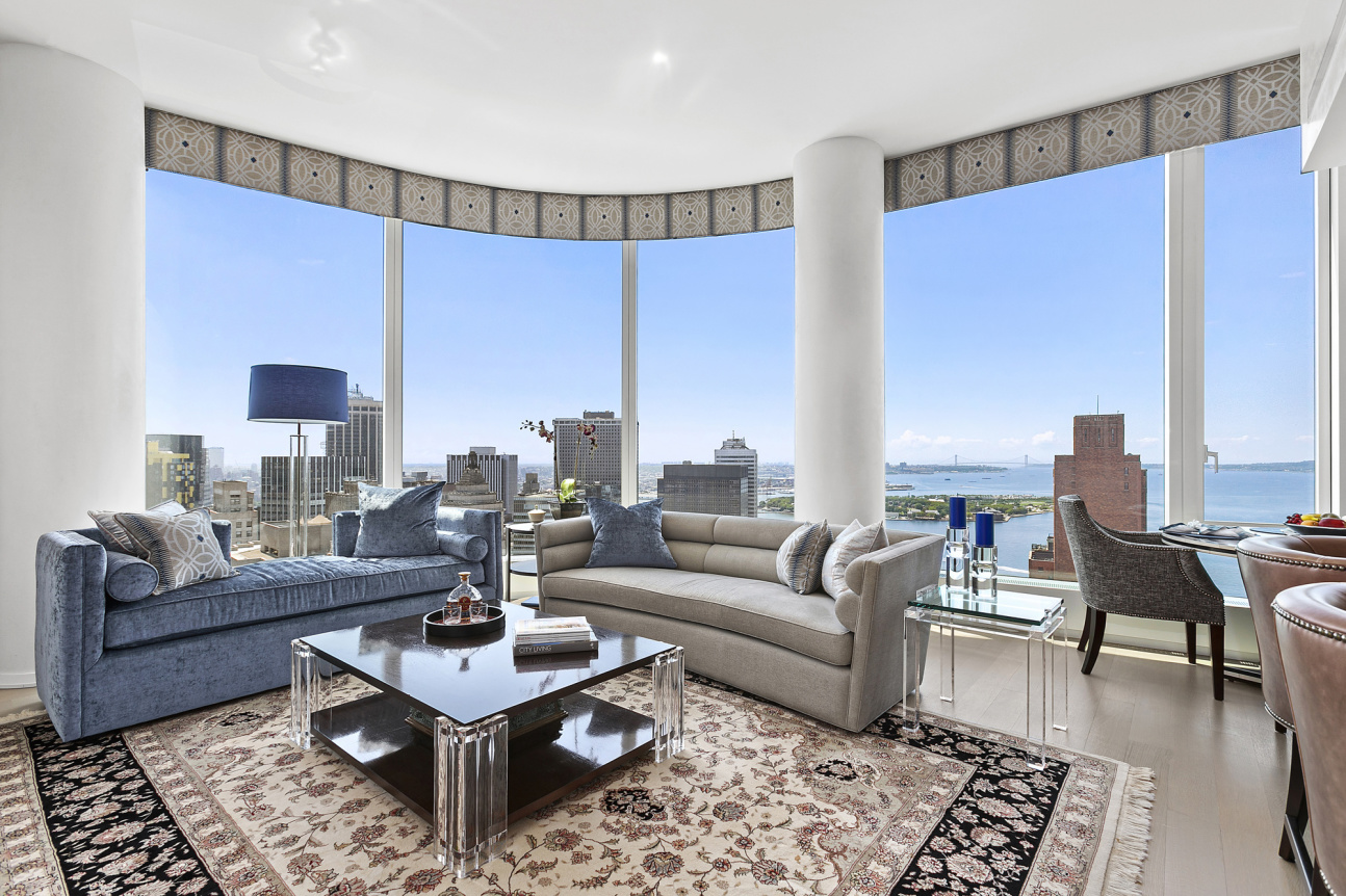 Offered furnished and unfurnished.Luxury living at its finest.Unparalleled City and New York Harbor views and extraordinary southern light make this 2 bedroom, 2-and-a-half bathroom home an exceptional place to live. 50 West is Downtown's premier full-service condominium.Perched high on the 45th floor and wrapped in curved windows to the south and east, this stunning 1,510-square-foot-home offers an inviting atmosphere. Ten-foot ceilings and designer lighting arise overhead and wide-plank wood floors run under foot. The expansive and airy great room provides for open living and dining leading to a fantastic kitchen with custom stained walnut cabinetry, granite countertops with waterfall island, Hansgrohe fixtures, and Miele and SubZero appliances. Appliances include a 4 burner gas cooktop, exterior vented exhaust hood, oven, speed oven, refrigerator, freezer, wine refrigerator, and dishwasher. Custom upgrades in the living room include built-in storage cabinets with a bar, an entertainer's dream.Two sunny bedroom suites are arranged in a split lay-out. The master suite offers city views to the south and east and includes a walk-in closet and a custom built-in wall of additional closet storage. The tranquil master bath features an extra-large, custom-sized shower, floating, backlit marble vanity, radiant floor heating, Hansgrohe polished chrome fixtures, and electronic Toto toilet with built-in bidet. The second bedroom offering southern harbor views features a custom built-in home office, perfect for working from home. The second bath and powder room both include marble wet walls and floors as well as custom vanities. There is a vented in- unit washer/dry and custom Lutron shades throughout the apartment.This home is available to rent furnished or unfurnished. Pets are case-by-case.50 West, a 64-story residential tower located in the center of the New Downtown, featuring Internationally-acclaimed architect Helmut Jahn and finishes by Thomas Juul-Hansen. State-of-the-art amenities include an immense Fitness Center, the beautifully-appointed Water Club, children's playroom and The Observatory at 50 West Street, a spectacular 64th floor outdoor entertaining space with infinite views of New York and beyond. Axiom Amenities also currently offers residents access to weekly virtual classes and activities for both adults and children alike, including exercise classes, cooking classes, movies of the week, and art activities for children.Transportation from this accessible location is unbeatable with 1/4/5 and /R/W trains all nearby.